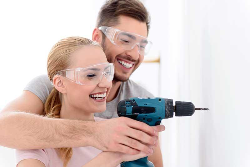 homme et femme heureux avec une perceuse